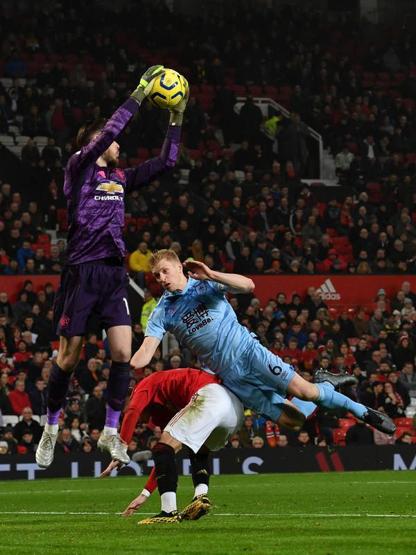 Kiper Manchester United, David de Gea menyelamatkan bola dari bek Burnley, Ben Mee dalam pertandingan pekan ke-24 kompetisi Liga Inggris 2019-2020 di Old Trafford, Rabu (23/1/2020). Manchester United (MU) tidak berdaya di kandang sendiri usai takluk 0-2 dari Burnley. (Paul ELLIS/AFP)