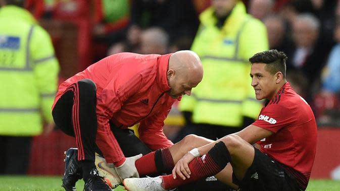 Winger Manchester United, Alexis Sanchez, mengalami cedera saat timnya menang 3-2 atas Southampton dalam laga pekan ke-29 Premier League, di Old Trafford, Sabtu (2/3/2019). (AFP/Oli Scarff)
