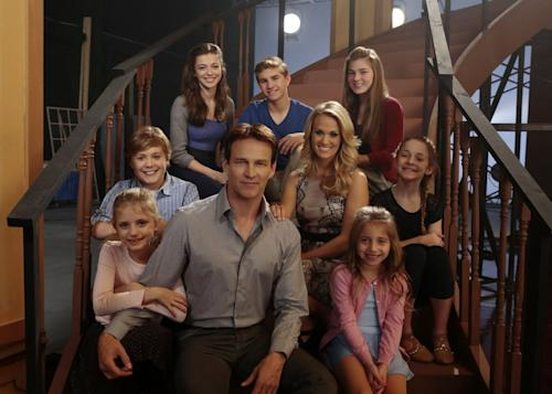 This image released by NBC shows Stephen Moyer as Captain Von Trapp, foreground center, and Carrie Underwood as Maria, second row center, with fellow castmates, clockwise from left, Grace Rundhaug as Marta, Joe West as Kurt, Ariane Rinehart as Liesl, Michael Nigro as Friedrich, Ella Watts-Gorman as Luisa, Peyton Ella as Gretl, Peyton Ella as Gretl on the set of The Sound of Music Live! in New York. The live production airs on Dec. 5 at 8 p.m. EST. (AP Photo/NBC, Giovanni Rufino)