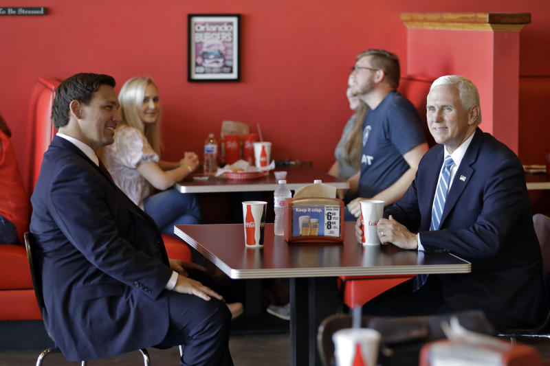 Vice President Mike Pence, right, talks to Florida Gov. Ron DeSantis as they wait for their lunch at Beth's Burger Bar, Wednesday, May 20, 2020, in Orlando, Fla. Pence is scheduled to participate in a roundtable discussion with hospitality and tourism industry leaders to discuss their plans for re-opening during the coronavirus outbreak. (AP Photo/Chris O'Meara)