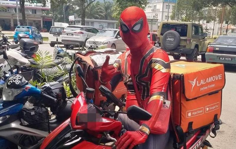 'Spiderman' was seen being questioned by the police at a roadblock last week. — Picture courtesy of Lalamove