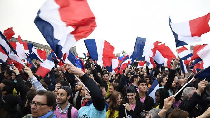 Pendukung mengibarkan bendera Prancis saat merayakan kemenangan Emmanuel Macron di luar museum Louvre, Paris, Minggu (7/5). Berdasarkan exit poll sejauh ini, rakyat Prancis memilih Macron sebagai presiden mereka yang baru. (AFP PHOTO/Eric FEFERBERG)
