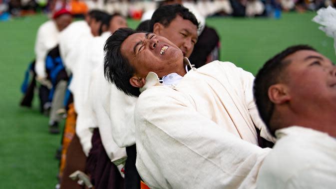 Para kontestan mengikuti kompetisi tarik tambang yang digelar di Wilayah Damxung, Daerah Otonom Tibet, China, 10 Agustus 2020. Dengan pakaian tradisional, para penggembala dari sejumlah desa di Wilayah Damxung berpartisipasi dalam permainan tradisional itu. (Xinhua/Purbu Zhaxi)