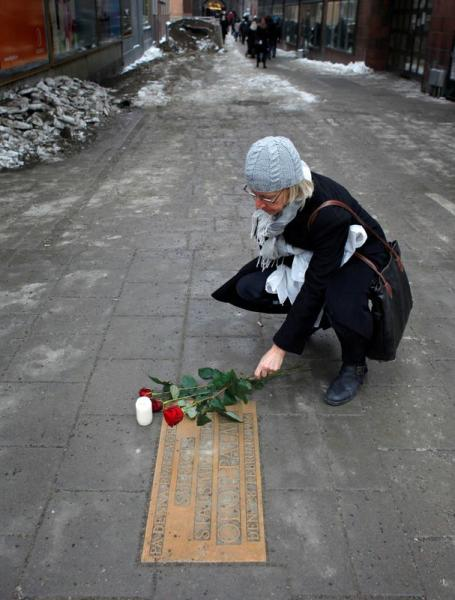 FILE PHOTO: A women lays a rose on a plaque marking the location where Swedish Prime Minister Olof Palme was killed 25 years ago in Stockholm