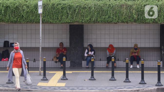 Sejumlah masyarakat melakukan jaga jarak aman di area publik di kawasan Thamrin, Jakarta, Rabu (18/3-2020). Jaga jarak atau prosedur social distancing measure harus diterapkan kepada masyarakat yang masih melakukan aktivitas di luar untuk memghindari penyebaran Covid-19. (Liputan6.com/Angga Yuniar)