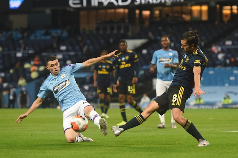 MANCHESTER, ENGLAND - JUNE 17: Phil Foden of Manchester City battles for possession with Dani Ceballos of Arsenal during the Premier League match between Manchester City and Arsenal FC at Etihad Stadium on June 17, 2020 in Manchester, United Kingdom. (Photo by Peter Powell/Pool via Getty Images)