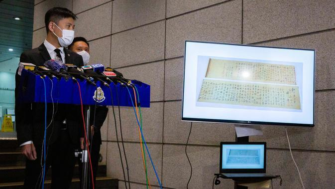 Polisi menunjukkan gambar gulungan kaligrafi karya Mao Zedong, yang telah ditemukan, pada konferensi pers di Hong Kong, 7 Oktober 2020. Gulungan sepanjang 2,8 meter itu ditemukan dalam keadaan terpotong menjadi dua bagian karena dianggap terlalu panjang untuk dipajang. (ISAAC LAWRENCE/AFP)