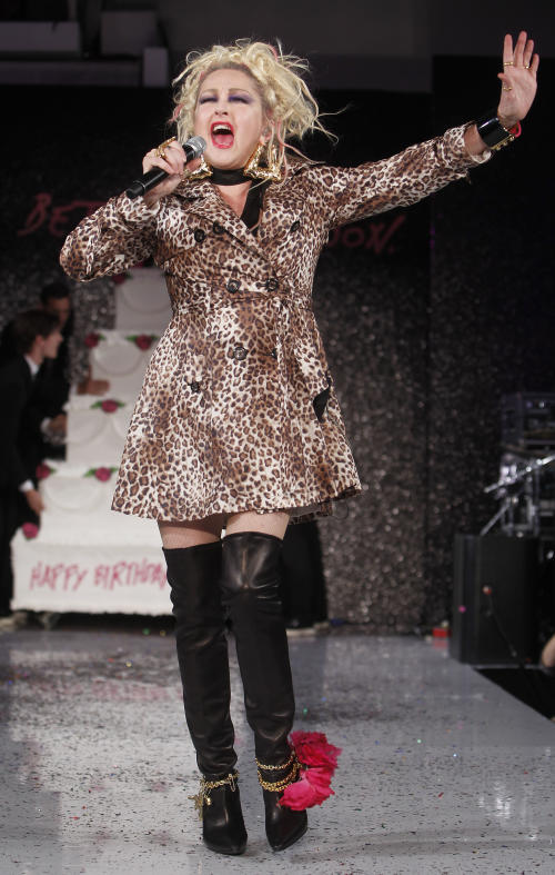 Singer Cyndi Lauper leads a birthday cake for designer Betsey Johnson onto the runway after the Betsey Johnson Spring 2013 collection show during Fashion Week, Tuesday, Sept. 11, 2012, in New York. (AP Photo/Jason DeCrow)