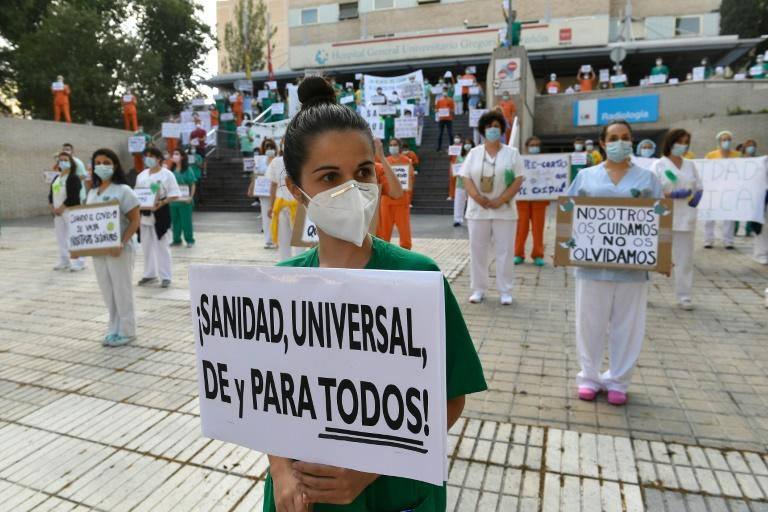 """Healthcare worker holds a sign reading """"Universal healthcare from and for all"""" during a protest in Madrid calling for reinforced healthcare as Spain begins 10-days mourning for those who died of coronavirus"""