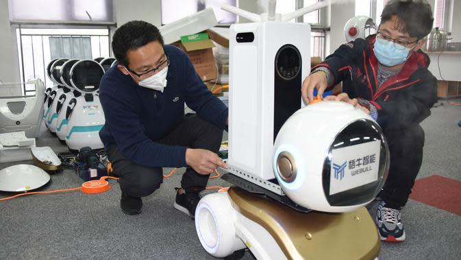 Para teknisi menyetel robot desinfeksi generasi kedua di sebuah perusahaan teknologi di Qingdao, Provinsi Shandong, China, 11 Februari 2020. Beberapa robot desinfeksi ini telah digunakan di ruang isolasi sejumlah rumah sakit di China. (Xinhua/Li Ziheng)