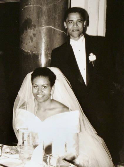 FILE-  This Oct. 18, 1992 file photo released by Obama for America shows President Barack Obama and first lady Michelle Obama on their wedding day in Chicago.  Obama's long-sleeve, portrait-collar wedding dress was one of her few fashion decisions that didn't move the needle. That was back in 1992, though.  Her one-shoulder, white inaugural gown by Jason Wu, however, turned into a bona fide bridal-gown sensation, says Miller. It came at the right time, as designers continued to move away from all strapless all the time, she observes, and Obama wore it with the right happy, confident attitude that brides strive for.    (AP Photo/Obama for America, file)   NO SALES
