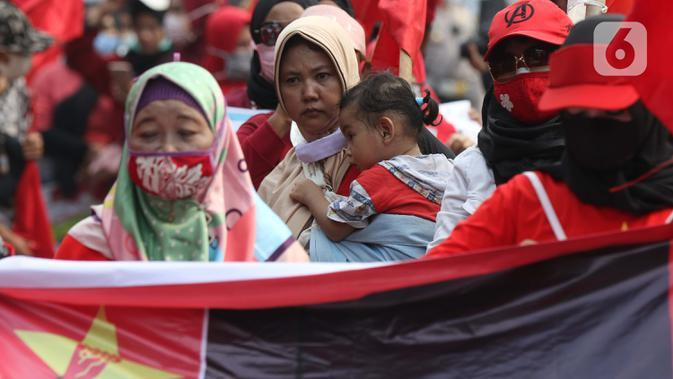 Seorang anak digendong terlihat dalam aksi unjuk rasa menolak UU Omnibus Law Cipta Kerja di Kawasan Patung Kuda, Jakarta, Jumat (16/10/2020). Meski sudah ada imbauan untuk tidak membawa anak-anak dalam aksi unjuk rasa namun sejumlah orang tua tetap menyertakan. (Liputan6.com/Helmi Fithriansyah)