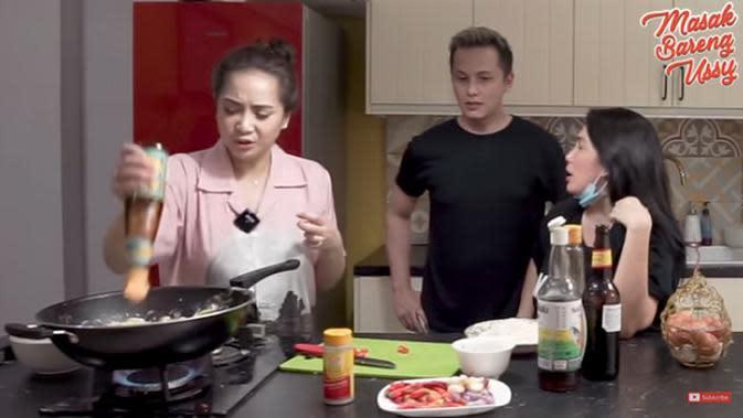 Gigi terlihat sibuk masak, sedangkan Ussy dan Andhika hanya melihat sambil berbincang. Gigi terlihat kesulitan mengeluarkan saus tiram yang hampir habis. Ia lantas mencari air panas untuk dimasukkan dalam botol. (Youtube/Ussy Andhika Official)
