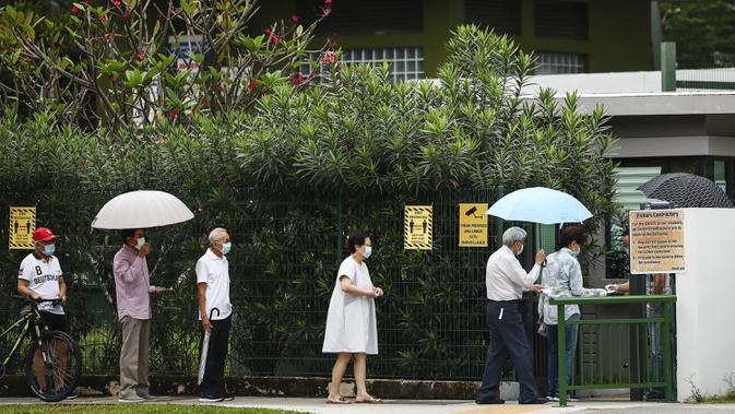 Para pemilih mengenakan masker dan menerapkan jaga jarak aman saat akan memberikan suara dalam pemilu di TPS Sekolah Dasar Alexandra, Singapura, Jumat (10/7/2020). Pemilu di tengah pandemi COVID-19, warga Singapura memberikan suaranya dengan mengenakan masker dan sarung tangan plastik. (AP Photo)