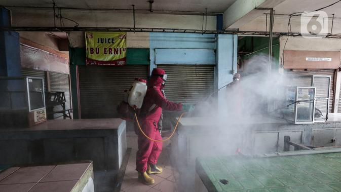 Petugas menyemprotkan Cairan Disinfektan di Pasar Palmerah, Jakarta, Kamis (25/6/2020). Penyemprotan dilakukan guna mencegah dan memutuskan mata rantai penyebaran Covid-19 di Area pasar Palmerah. (Liputan6.com/Johan Tallo)