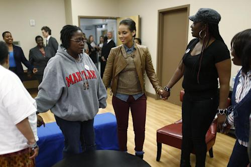 "Grammy Award-winning singer Alicia Keys, center, stands in the middle of a prayer circle of HIV positive women as she visits an HIV women's support group at United Medical Center in Washington, Monday, April 15, 2013. Keys is working with the Kaiser Family Foundation for ""Empowered,"" a campaign launched last month to educate women about HIV/AIDS and provide grants to community based projects that will do that. (AP Photo/Charles Dharapak)"