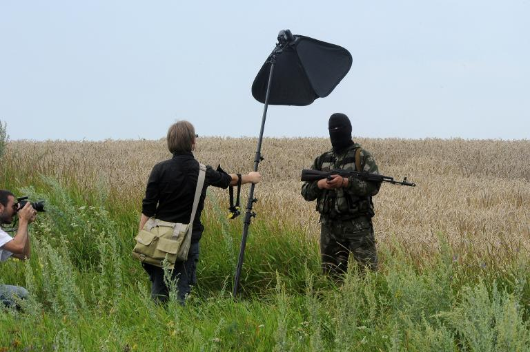 A masked armed separatist militant poses for a photographer near the site of the MH17 plane crash in eastern Ukraine, on July 19, 2014