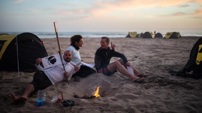 Peserta beristirahat setelah babak kedua Half Marathon des Sables di Gurun Ica, Paracas, Peru, Selasa (3/12/2019). Masing-masing peserta harus membawa semua yang mereka butuhkan untuk bertahan hidup selama lomba. (Martin BUREAU/AFP)
