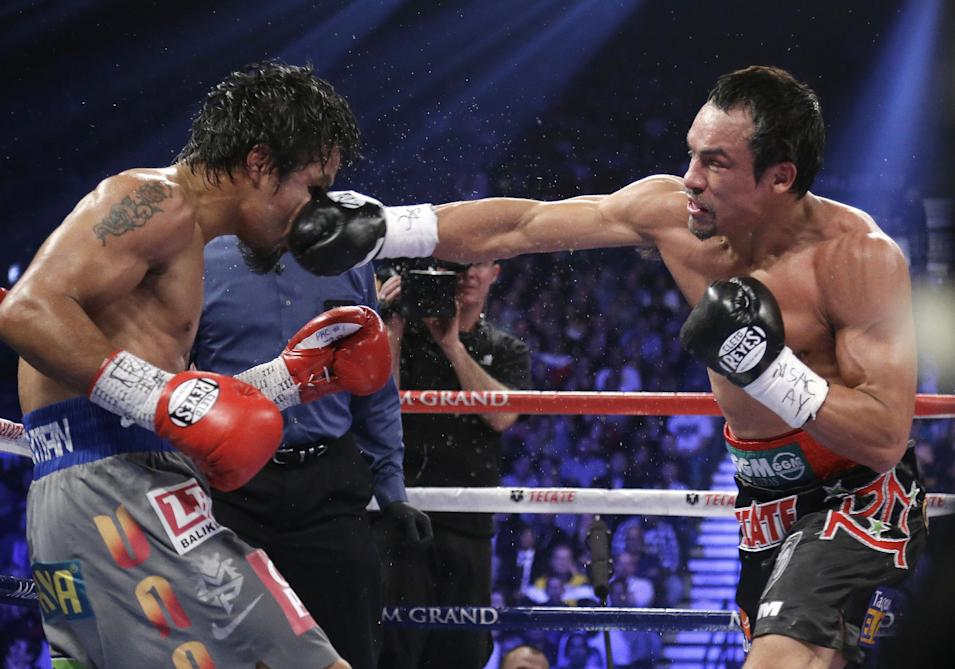 Juan Manuel Marquez, from Mexico, right, lands a right to the head of Manny Pacquiao, from the Philippines, during their WBO world welterweight  fight Saturday, Dec. 8, 2012, in Las Vegas. Marquez won by a knockout. (AP Photo/Julie Jacobson)