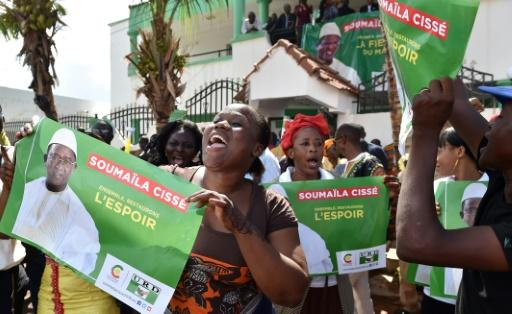 """Supporters of Malian opposition leader and presidential candidate Soumaila Cisse hold posters reading """"Together, let's restore hope"""""""