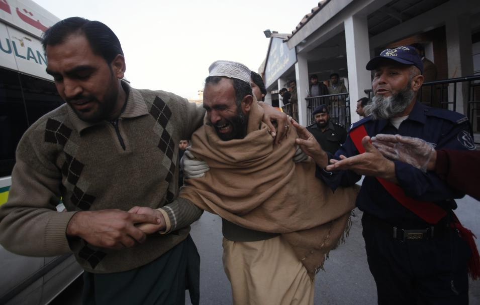 People comfort a man over the death of his brother who died in a grenade attack in Peshawar