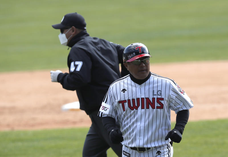 "A letters reading ""Corona 19 Out"" is seen on the helmet of LG Twins baseball team's coach Kim Ho as third base umpire Choi Young-joo, left, wearing a mask and gloves as a precaution against the new coronavirus runs during the pre-season baseball game between Doosan Bears and LG Twins in Seoul, South Korea, Tuesday, April 21, 2020. South Korea's professional baseball league has decided to begin its new season on May 5, initially without fans, following a postponement over the coronavirus. (AP Photo/Lee Jin-man)"
