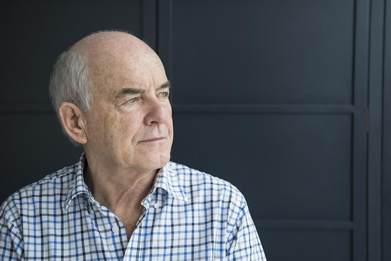 An older man with male pattern baldness looks out a window