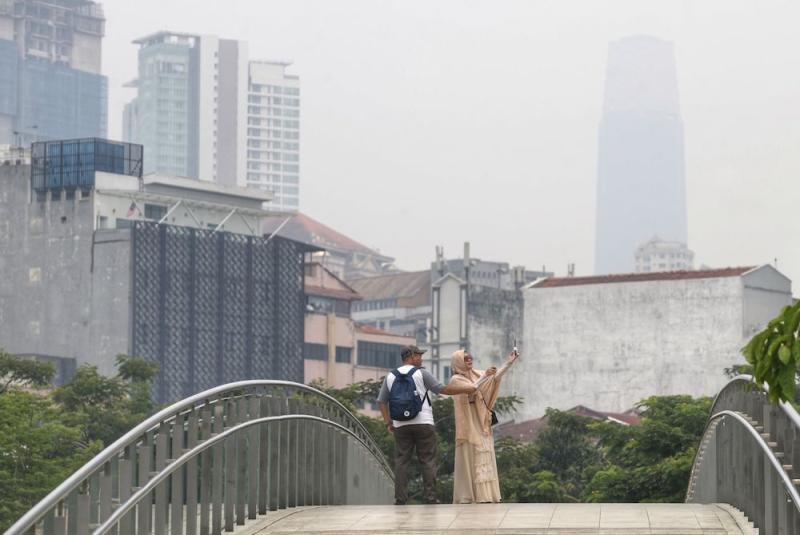 Tourists take a selfie as haze blankets Kuala Lumpur September 12, 2019. — Picture by Ahmad Zamzahuri