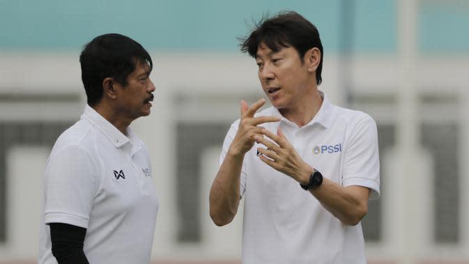 Manajer pelatih Timnas Indonesia, Shin Tae-yong, berbincang dengan Indra Sjafri, saat sesi latihan di Stadion Wibawa Mukti, Cikarang, Senin (13/1/2020). Sebanyak 51 pemain mengikuti seleksi untuk memperkuat skuat utama Timnas Indonesia U-19. (Bola.com/M I