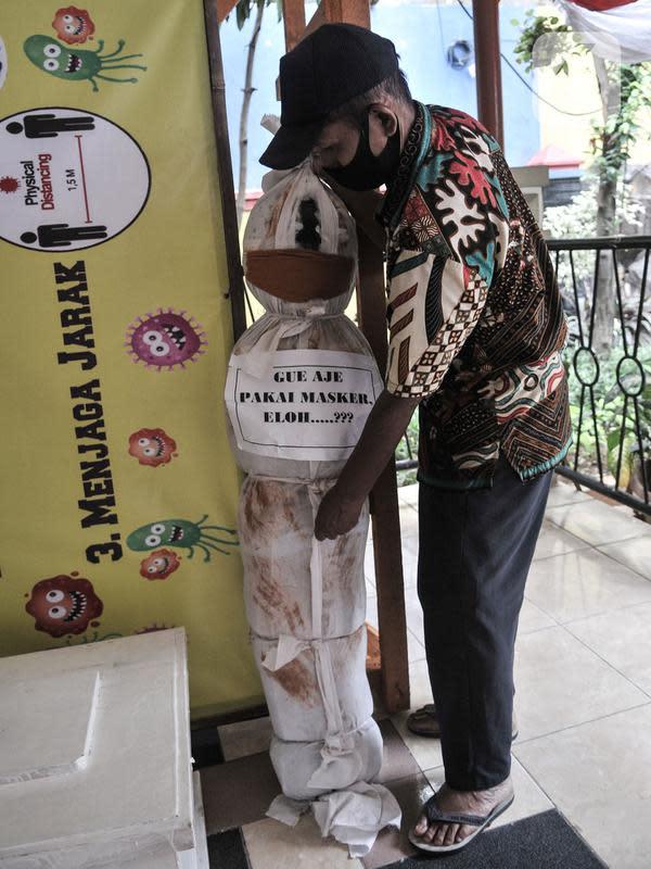 Pekerja memasang boneka pocong di Kantor Kecamatan Senen, Jakarta, Kamis (13/8/2020). Pemkot Jakpus menyiapkan peti mati dan boneka pocong untuk dipajang di setiap kecamatan sebagai peringatan akan bahaya Covid-19 dan imbauan untuk tidak mengabaikan protokol kesehatan. (merdeka.com/Iqbal Nugroho)