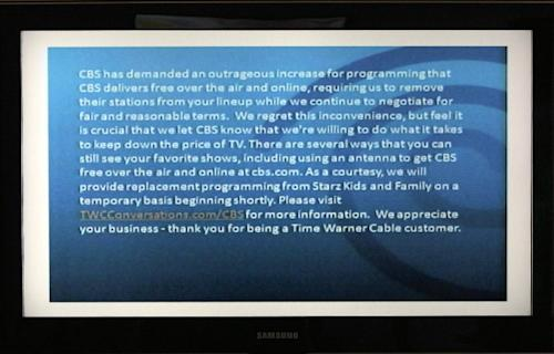 FILE - This Aug. 2, 2013 file photo, a television screen shows the CBS channel with an announcement by Time Warner Cable in Los Angeles. There's been no reported progress in negotiations between CBS Corp. and Time Warner, which has blocked CBS programming from its customers' homes in Dallas, Los Angeles and New York since Aug. 2. They are at odds over a deal to carry CBS on Time Warner, most prominently over retransmission fees that the cable operator pays to CBS per subscriber. Talks are expected to continue over the Labor Day weekend. Meanwhile, Time Warner customers caught in the middle will miss third and fourth round competition in the U.S. Open tennis tournament. The tournament's finals are next weekend, along with opening weekend in the National Football League. (AP Photo/Nick Ut)