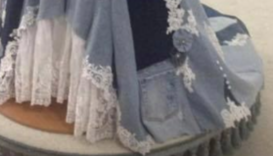 A denim back pocket on the hem of a denim and lace gown's skirt