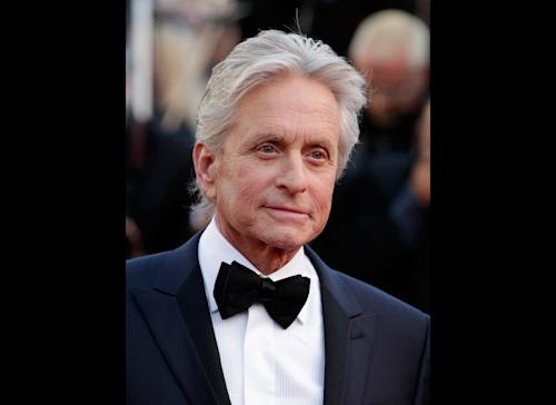 FILE - Actor Michael Douglas poses for photographers as he arrives for the screening of Behind the Candelabra at the 66th international film festival, in Cannes, southern France, in this May 21, 2013 file photo. The Guardian newspaper published an interview Monday June 3, 2013 in which Douglas blamed cunnilingus for the grave malady that was diagnosed in 2010. The newspaper also quoted doctors who were skeptical about his claim. (AP Photo/David Azia, File)