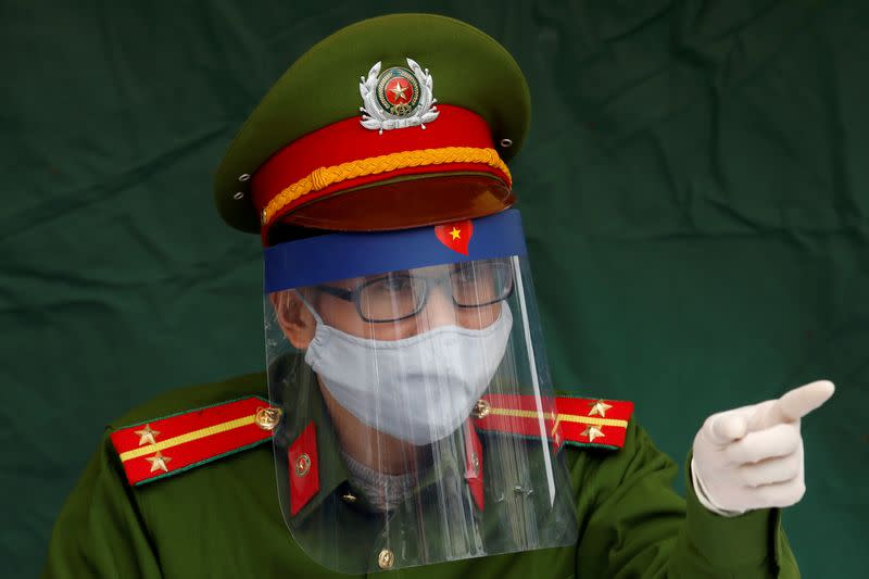 FILE PHOTO: Police officer Nguyen Tien Thanh wears a protective face shield as he takes the duty at a health check point on a road during coronavirus disease (COVID-19) outbreak in Hanoi
