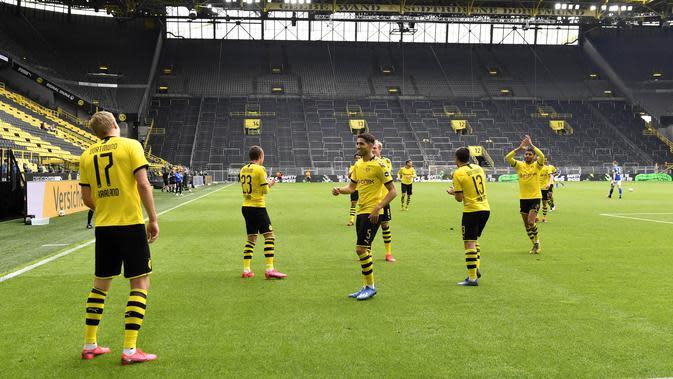 Para pemain Borussia Dortmund merayakan gol yang dicetak oleh Erling Haaland ke gawang Schalke 04 pada laga Bundesliga di Stadion Signal Iduna Park, Sabtu (16/5/2020). Pandemi COVID-19 membuat pemain melakukan selebrasi jaga jarak. (AP/Martin Meissner)