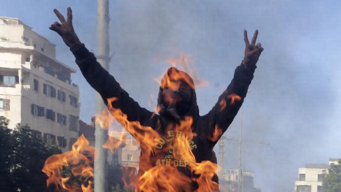 Demonstran antipemerintah meneriakkan slogan-slogan dekat kobaran api saat protes menentang elite penguasa di Kota Jal el-Dib, Lebanon, Selasa (14/1/2020). Demonstran menganggap elite penguasa gagal mengatasi ekonomi yang menurun tajam. (AP Photo/Hassan Ammar)