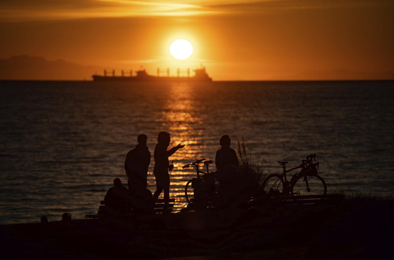 A woman is silhouetted while taking in the sunset with others at English Bay Beach, as a freighter is anchored in the distance off Vancouver, British Columbia, Saturday, March 21, 2020. The City of Vancouver asked those coming to the park and beach to maintain a distance of two meters between one another due to concerns about the spread of the coronavirus. (Darryl Dyck/The Canadian Press via AP)
