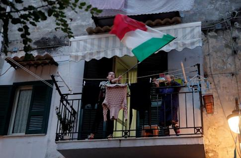 A woman in Naples waves an Italian flag on a balcony on Friday, the fourth day of a lockdown across all of Italy. Photo: Reuters