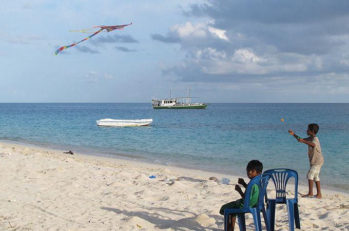 Some of the local boys fly kites on the shore. Photo: Roderick Eime