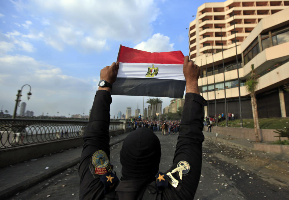 A police officer holds the Egyptian national flag during clashes with anti-government protesters, background, near Tahrir Square, Cairo, Egypt, Tuesday, Jan. 29, 2013. Intense fighting for days around central Tahrir Square engulfed two landmark hotels and forced the U.S. Embassy to suspend public services on Tuesday. (AP Photo/Khalil Hamra)
