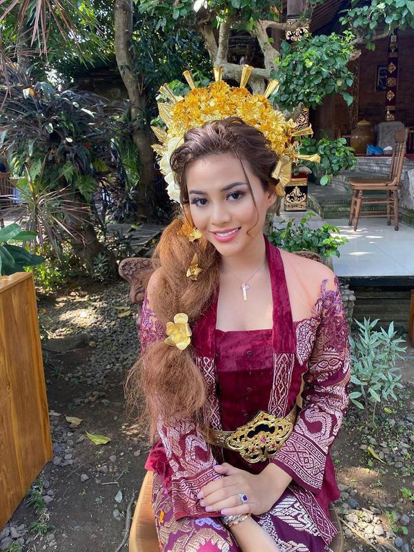 Tak mau kalah dengan sang bunda, Aurel Hermansyah pun juga berdandan ala perempuan Bali. Ia memakai kebaya bludur berwarna ungu yang dipadukan dengan hiasan kepala dan belt yang berwarna emas. (Instagram/aurelie.hermansyah)