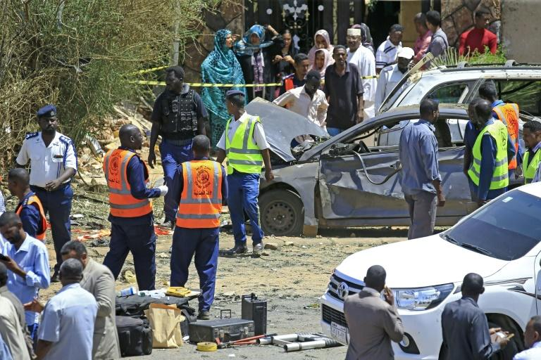 Sudanese rescue teams and security forces circle damaged vehicles at the site of a bomb attack targeting the convoy of Prime Minister Abdalla Hamdok, who survived the attack unharmed