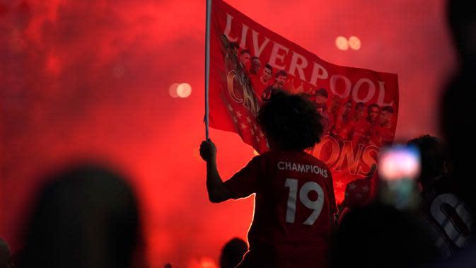 Seorang pendukung Liverpool merayakan gelar juara Liga Premier di luar Stadion Anfield, Kamis (25/6/2020). Trofi juara Liga Primer musim 2019-2020 Trofi juara Liga Primer musim 2019-2020 tersebut dimenangkan Liverpool setelah Manchester City takluk 1-2 dari Chelsea. (AP/Jon Super)