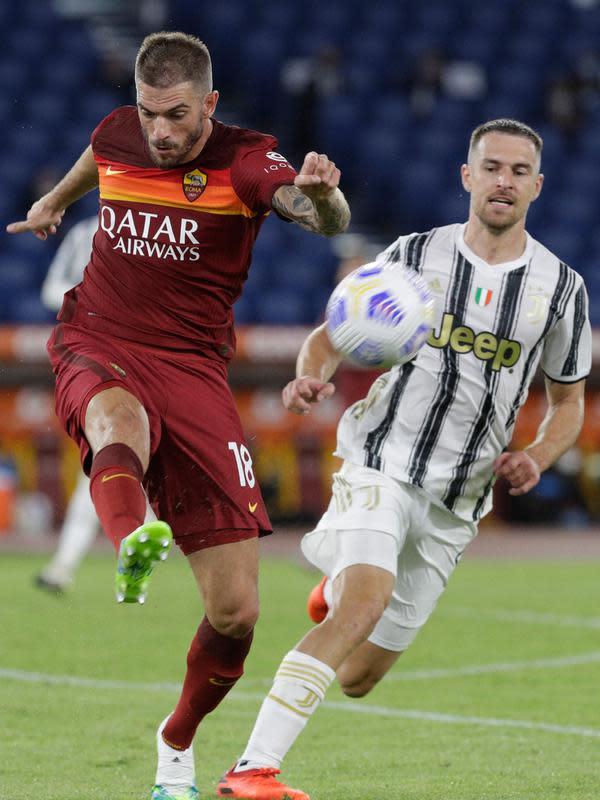 Bek AS Roma, Davide Santon menendang bola melewati gelandang Juventus, Aaron Ramsey pada pekan kedua Liga Italia Serie A 2020-2021 di Stadion Olimpiade Roma, Minggu (27/9/2020). Juventus bermain imbang 2-2 di kandang AS Roma. (AP Photo/Gregorio Borgia)