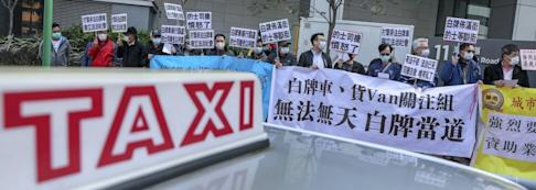 Taxi drivers hold up banners pointing to Uber's illegal status in Hong Kong at a demonstration outside the West Kowloon Government Offices in Yau Ma Tei in February. Photo: Winson Wong
