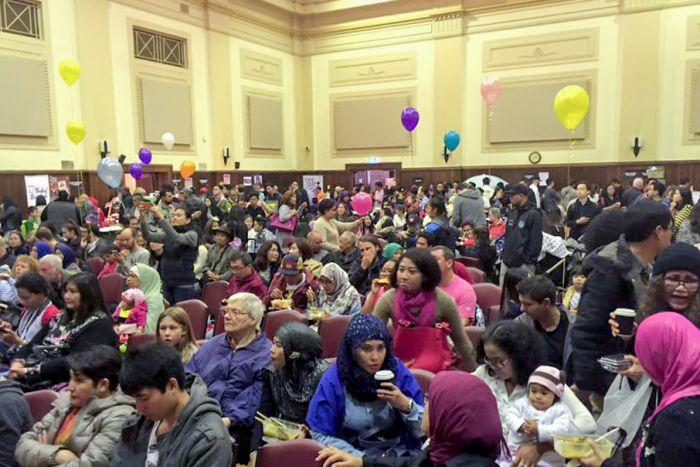 People in seats in a hall, balloons.