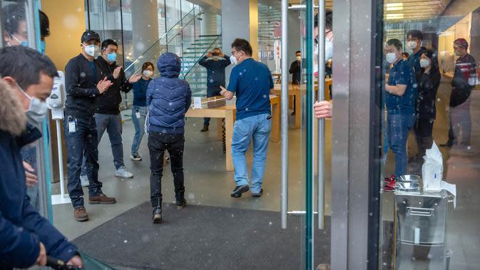 Pekerja bertepuk tangan saat pelanggan memasuki Apple Store yang dibuka kembali di Beijing, China, Jumat (14/2/2020). Pelanggan yang yang akan memasuki toko diminta menggunakan masker dan mau mengikuti pengecekan suhu tubuh. (AP Photo/Mark Schiefelbein)