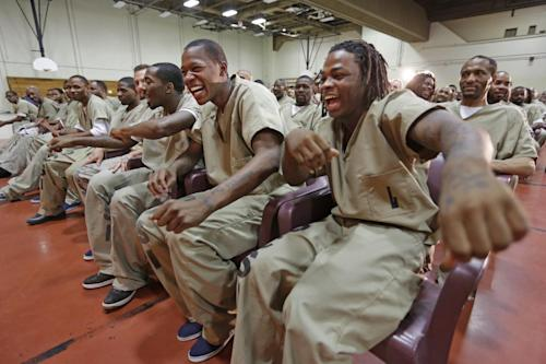 "In this Aug. 27, 2013, photo, inmates, from left, Eric McNeil, Kevin Fields, and Julian Campbell, dance in their seats while watching rappers perform a hip hop adaptation of William Shakespeare's Othello, titled ""Othello: The Remix"" at the Cook County Jail in Chicago. Campbell, 19, said the play offered two lessons: ""Be honest. Always think before you do."" Fields, also 19, saw the play as a cautionary tale. ""You can't affect what other people do but you can affect what you do,"" he says. The show was an eye-opener in another way: ""In hip-hop,"" he adds, ""I finally found out what Shakespeare really is."" (AP Photo/M. Spencer Green)"