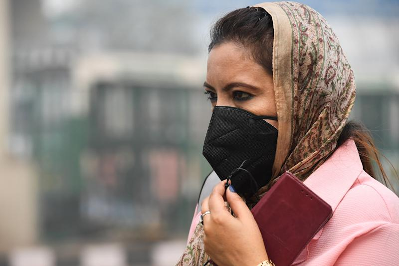 A woman wearing a protective face mask waits for public bus in smoggy conditions in New Delhi on Nov. 4, 2019. (Photo: Prakash Singh/AFP via Getty Images)