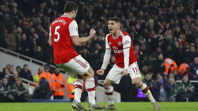 Bek Arsenal, Sokratis Papastathopoulos, melakukan selebrasi bersama Lucas Torreira usai membobol gawang Manchester United pada laga Premier League di Stadion Emirates, Rabu (1/1/2020). Arsenal menang 2-0 atas Manchester United. (AP/Matt Dunham)